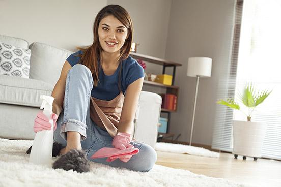 Frau reinigt Teppichboden
