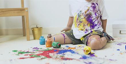 Kind verschuettet Farben und verursacht Flecken