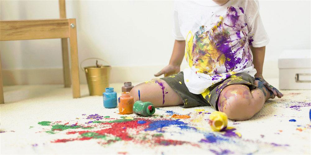 Leere Farbeimer stehen auf verschmiertem Teppich